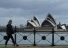 a masked woman walks by sydney opera house