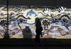 a woman walks past a mural with indigenous themes and native animals