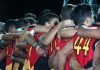 aboriginal football players stand with their arms around each others shoulders