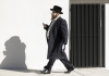 an orthodox jewish man walks down a street in traditional clothing