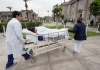 Healthcare workers transport a patient on a hospital bed between hospital buildings.