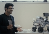 Dr Eduardo Benitez Sandoval beside a four-wheeled robot used in the Creative Robotics Lab