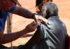 A senior Aboriginal man receiving a COVID-19 vaccine