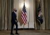 joe biden walks past american flags to a press briefing