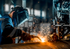 Person welding metal with sparks flying in a factory.