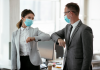 Two people in the workplace with masks on knocking elbows in greeting.