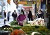 People wearing masks shopping at an outdoor fruit market