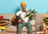 Person holding French Bulldog and plant sitting on couch in apartment.