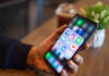 Person holding iphone with focus on social media apps in folder.