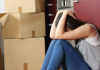 Woman in despair surrounded by moving boxes