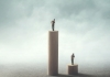 A man standing on a tall tower looking down on a man on a small tower