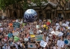 Crowds of people with signs and a globe of the world gather before a building to protest against climate change