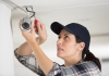 Woman installing security camera