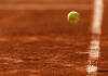 A tennis ball bounces on a clay court