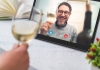 A hand holds a glass of white wine toasting a man on an iPad screen holding a glass of white wine