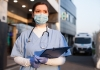 Young female EMS key worker doctor in front of healthcare ICU facility, wearing protective PPE face mask equipment, holding medical lab patient health check form