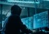 A man wearing a hood looking at computer screens.