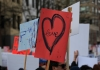 a red sign with a love heart at a protest