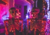 Two skeleton Halloween decorations in neon light
