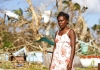 Woman stands in front of her destroyed home in Vanuatu