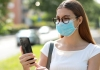 Woman using phone wearing face mask in public