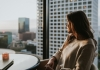 Young woman at table looks out at city skyline
