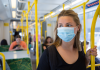 A young woman wearing a face mask riding public transport