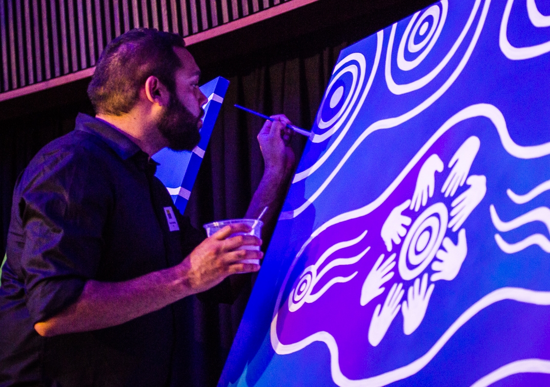 """Artist Dennis Golding works on the painting """"Pathways to Our Right"""" at the launch of the Australian Human Rights Institute at UNSW Sydney. Photo: Diane Macdonald"""