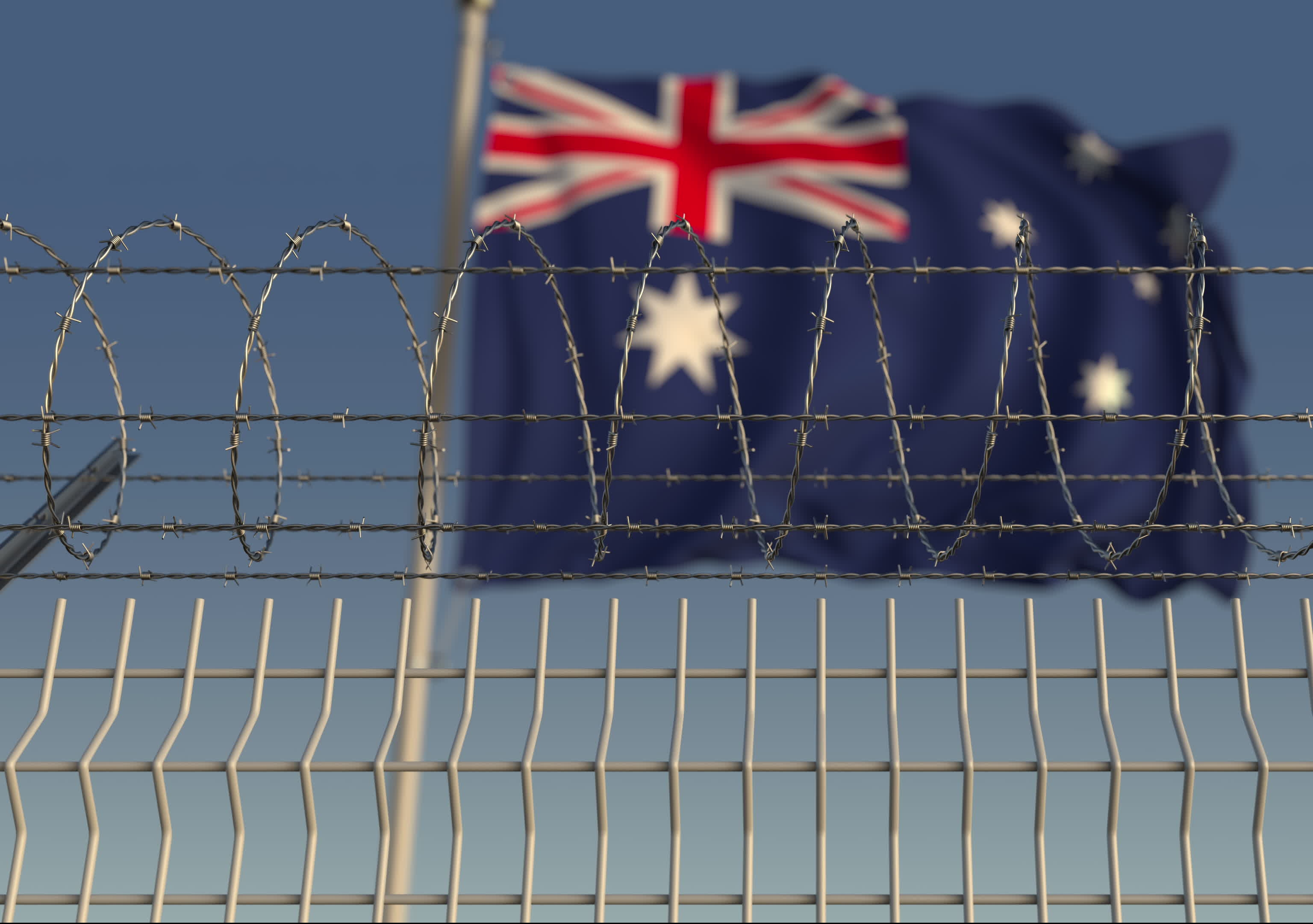 A blurred Australian flag waving behind a barbed wire fence. Image: Shutterstock