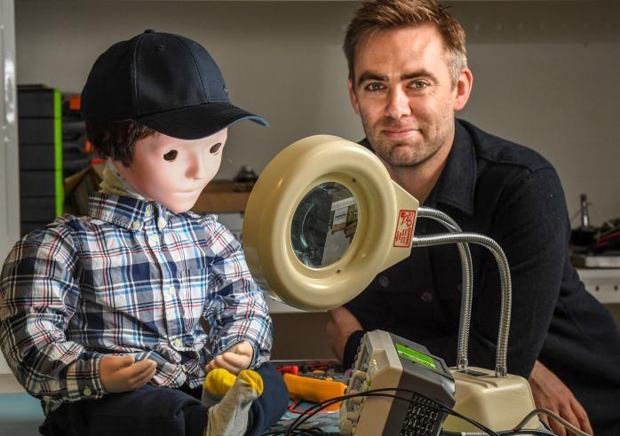 A social robot, Kaspar, looking into a mirror beside researcher Dr Scott Brown