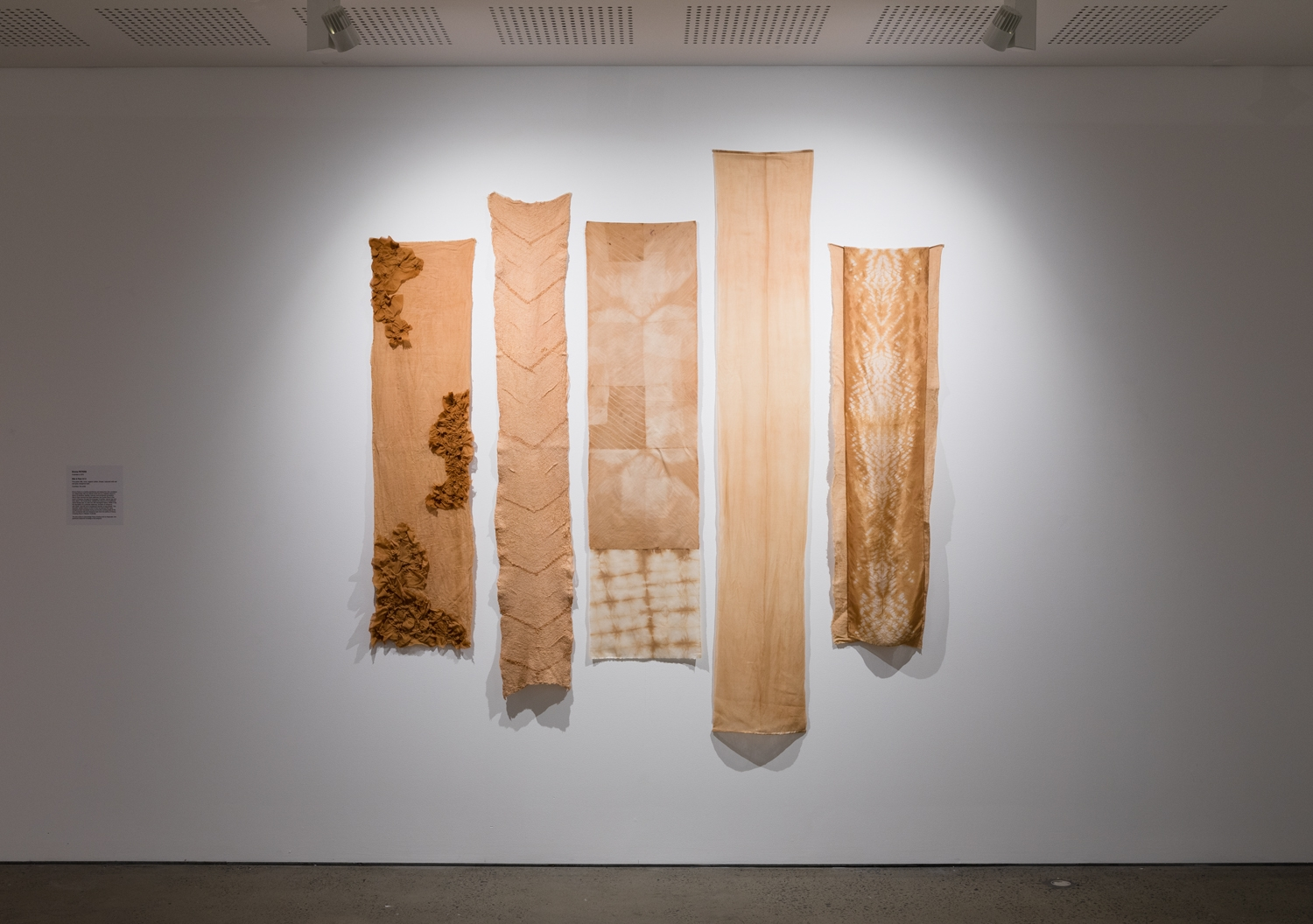 Five lengths of textiles hung on a wall, in warm apricots and earthy browns representing the Cooks River, by Emma Peters