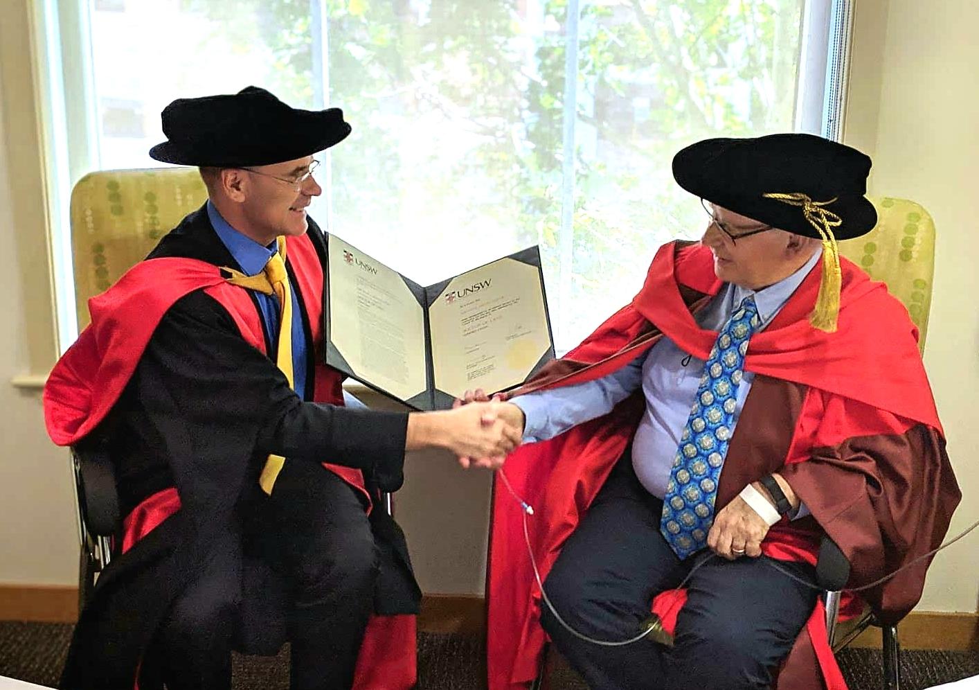 UNSW Dean of Law, Professor George Williams (left) confers the honorary doctorate on Emeritus Professor Michael Coper.