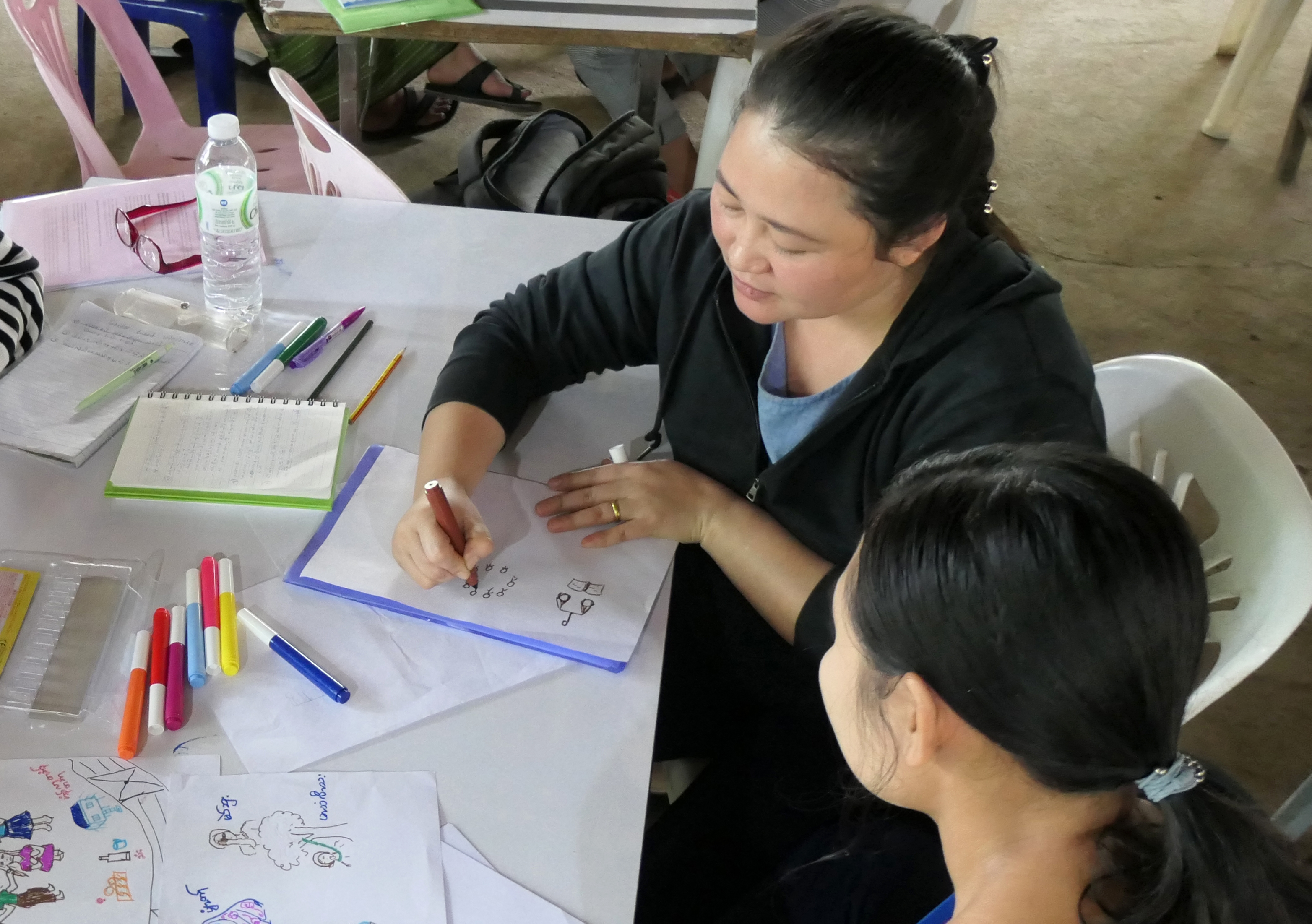 Refugee women drawing storyboards seated at a desk
