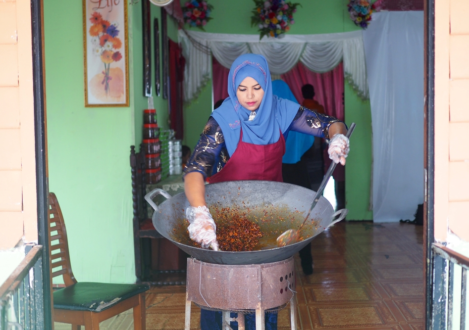 A woman ladles chilli paste in a large wok in her home