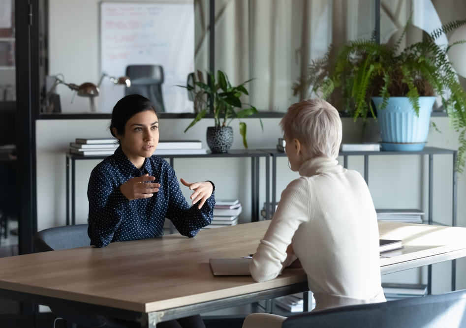 Two women at office meeting.