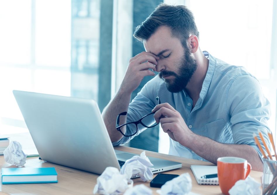 Frustrated young beard man massaging his nose and keeping eyes closed while sitting at his working place in office